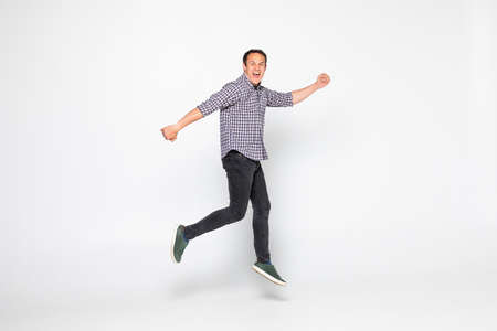 Cheerful young man jumping over a white background
