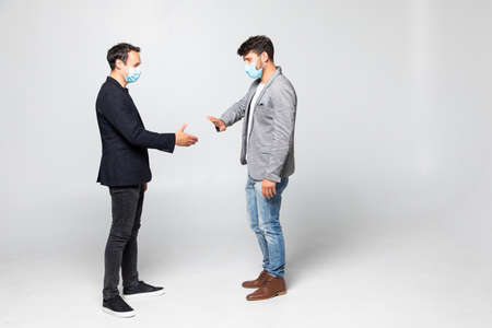 Two people in suits refuse to greet each other in a meeting traditional handshake of covid situation in the world isolated on a white background.
