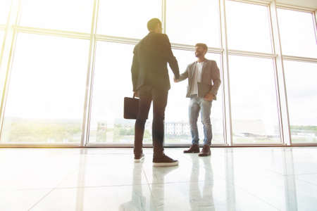 Two businessmen handshake in office with big panoramic windows
