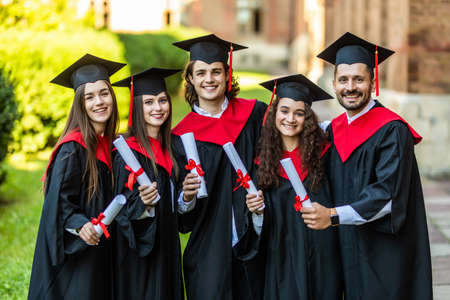 Close-up of five graduates posing in front of the university Zdjęcie Seryjne