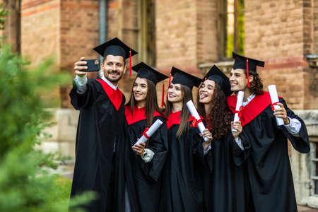 Four college graduates in graduation gowns standing close to each other and making selfie