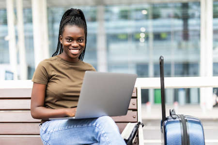 Young african woman with hand luggage in airport terminal, working on her laptop while waiting for flight