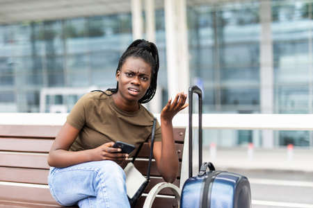 Sad african woman with suitcase in airport waiting flight.