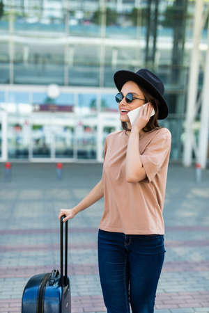 Young woman with suitcase walks along the airport and talks on the phone Banque d'images