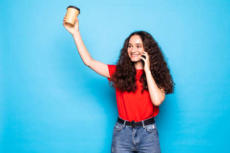 Beautiful young woman talking phone and holding a take away coffee on the blue background