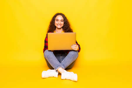 Portrait of a young woman sitting cross-legged using a laptop, on a yellow background
