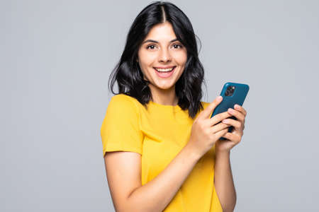 Attractive young woman holding smart phone and looking at it with smile while standing against gray background
