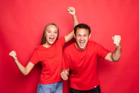 happy couple won emotionally celebrating win on red background Reklamní fotografie