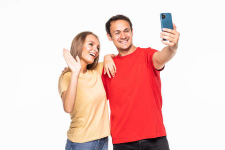 Young couple making a selfie or video call together with a mobile phone in white background