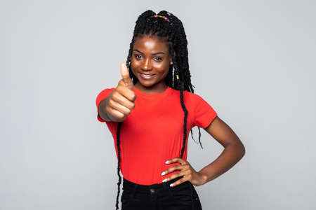 Smiling african American young woman show thumbs up recommend good service isolated on gray studio background