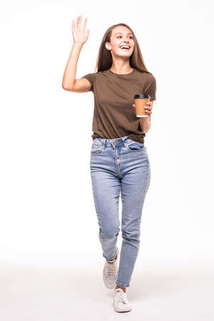 Thoughtful young woman greeting someone holding coffee walking on white background