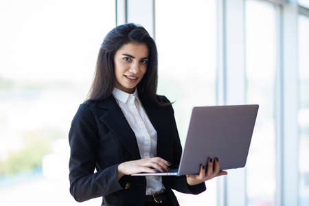 Modern business woman typing on laptop computer while standing in the office before meeting or presentation