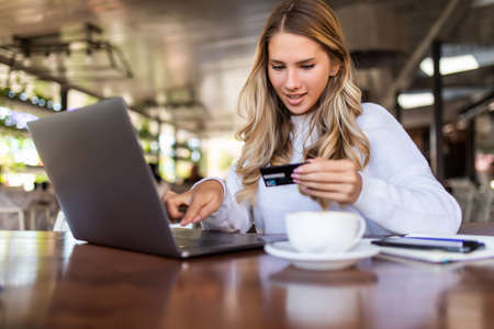 Happy woman using credit card and laptop for shopping while sitting in cafe. Фото со стока