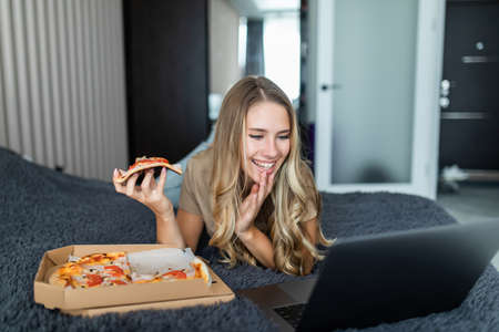 Portrait of young girl sitting on a bed with a box of pizza, biting a piece of pizza. Happy woman eating pizza for breakfast. Stock Photo