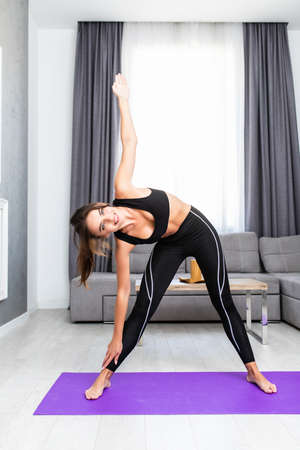 Young woman doing exercise Yoga pose in the bedroom