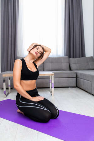 Joyful young female is doing stretching exercises on mat in living-room Reklamní fotografie