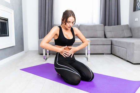 Young woman doing vacuum exercise on floor in living room at home
