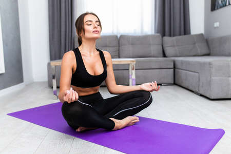 Young woman doing yoga on a gym carpet in the living room Reklamní fotografie