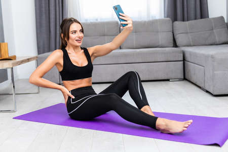 Beautiful young woman in sports clothing using her smart phone, makes selfie while doing yoga at gym
