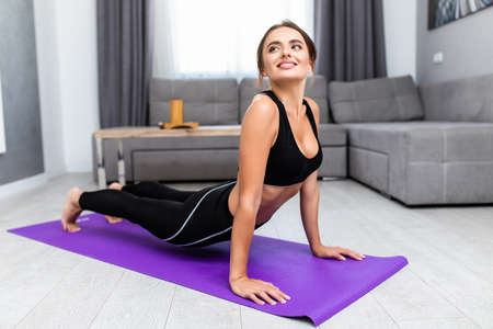 Attractive and healthy young woman doing exercises while resting at home