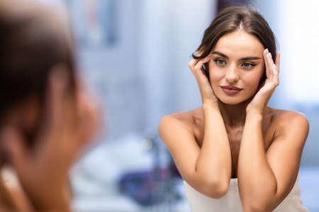 selective focus of beautiful smiling young woman touching face while looking at mirror