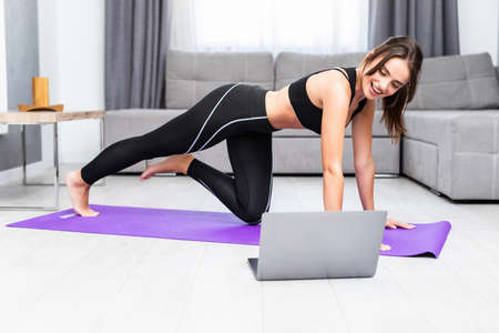 Young woman exercising at home in a living room. Video lesson. Young woman repeating exercises while watching online workout session.