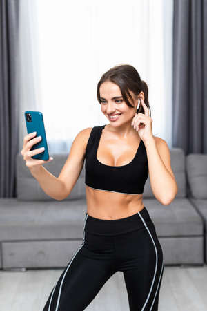 Fitness girl listening to music with earphones and smart phone sitting on the floor at home 免版税图像