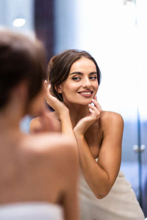 beautiful smiling young woman in bathrobe and towel on head looking at mirror in bathroom Reklamní fotografie