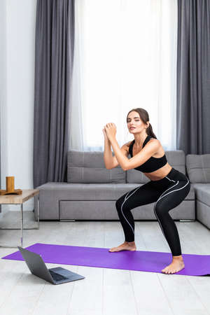 Attractive young woman in sportswear doing sit-ups in living room, training legs squatting at home.