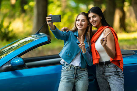 Two cheerful young women sitting on car and taking selfie with mobile phone Standard-Bild