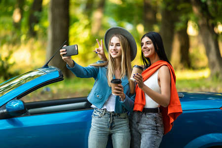 Two attractive young women taking selfe in a convertible car