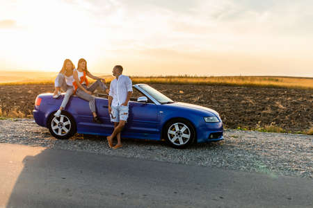 Young friends standing near convertible car and talking each other have fun on beauty sunset on the road