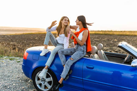Young pretty two women sitting on convertible car and talking spend free time together.