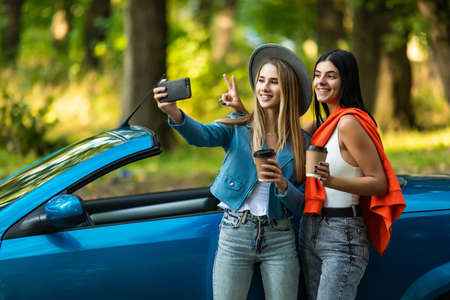 Two attractive young women holding coffee cup taking selfe in a convertible car on summer day Standard-Bild