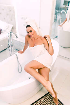 Beautiful woman covered her body with white towel looking away thinking standing near bathtub.