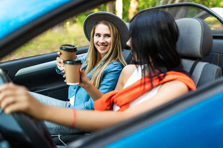 Portrait of two happy smiling girls drinking coffee while riding in car at sunset. Imagens