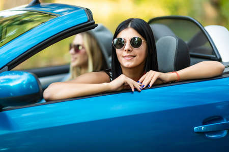 Close up of women wearing sunglasses in the white car. Little holiday trip of friends