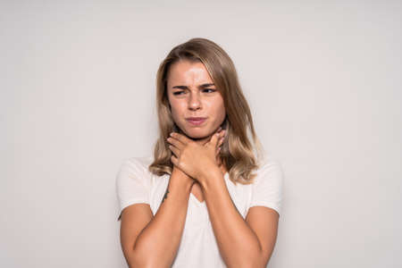 Young woman with sore throat on white background