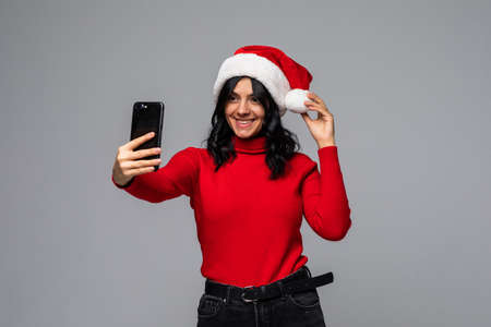 Young woman in santa hat take selfie on the phone isolated on gray background Stock Photo