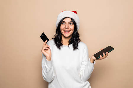 Happy young woman shopping with credit card and mobile phone on Christmas isolated