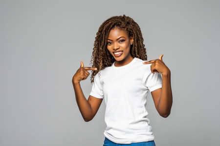 Positive African American woman indicates at herself, expresses surprises, can not believe friend fell in love with her, looks with disbelief at camera, stands against white background