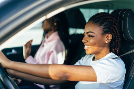 Two Female Friends On Road Trip Driving In Convertible Car