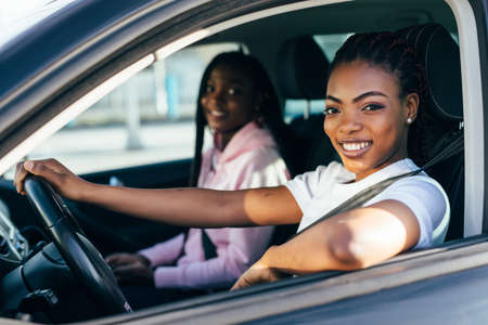 Two beautiful african young cheerful women looking at each other with smile while sitting in car