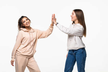 Portrait of two attractive mixed race women laughing and giving high five over white background Imagens