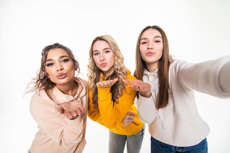 Three young beautiful mischievous ladies blowing kisses across their hands as they stand close together in a row isolated on white Stock Photo