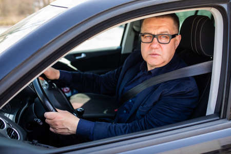 Handsome middle age man driving a car Stock Photo