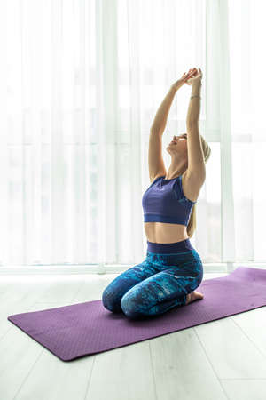Cross-Body Shoulder Stretch. Sport Woman at home does a warm up and stretch.