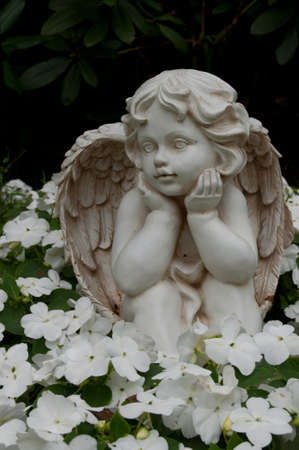 Angel figure in a bed at the cemetery. photo