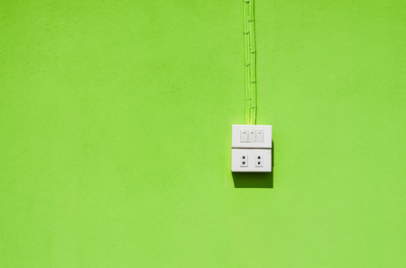 switch plug: the white electric switch and plug on the green wall