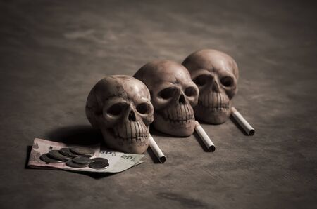 losing money: still life style of skull with dying and losing money of cigarette